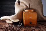 Coffee cup coffee mill and coffee beans on wooden table