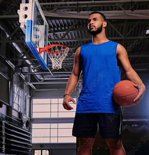 Fotobehang Basketbal Basketball player holds a ball over the hoop in a game hall.
