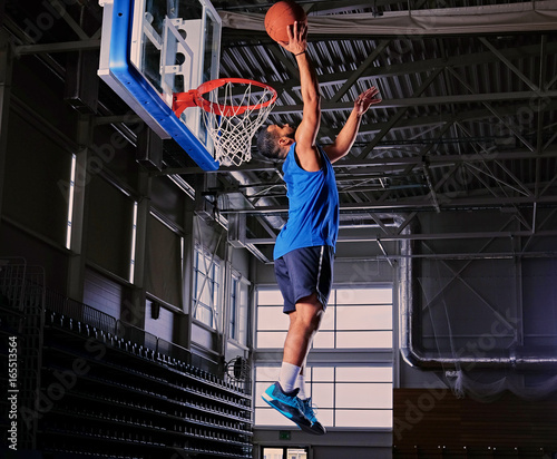 Fotobehang Basketbal Black professional basketball player in action on a basketball field.