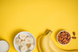 A banch of bananas and a sliced banana in a dish over yellow background. - 165519340