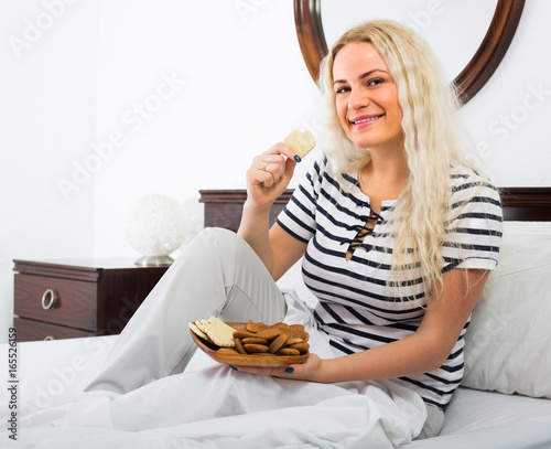 Young woman with biscuits in bed.