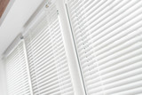 Windows with white venetian blinds.