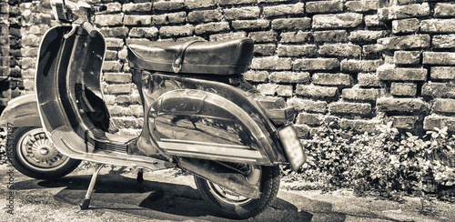 Aluminium Scooter MILANO, ITALY - SEPTEMBER 25, 2015: Old Vespa parked along Navigli at night. Vespa is an old italian motorbike