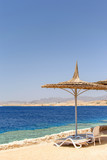 Beach umbrellas in front of coral reef and red sea - 165543508
