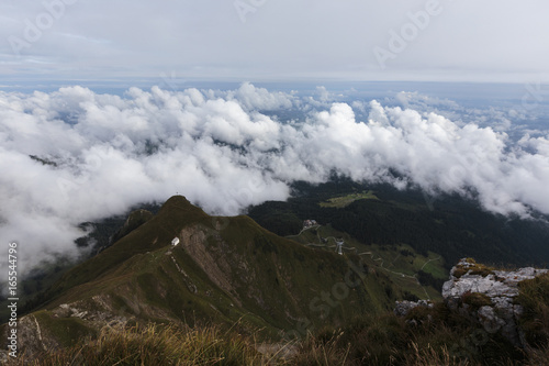 View of a small white church in the Swiss Alps amongst a cloudy landscape