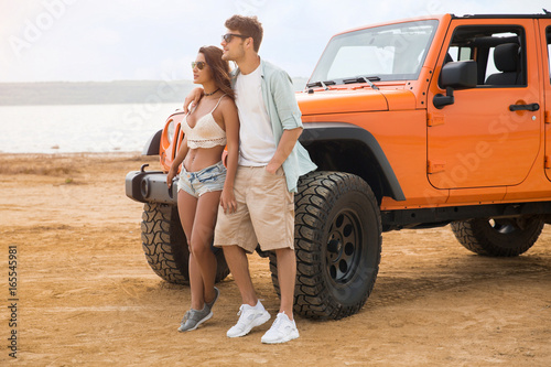 Beautiful young couple standing together near their car