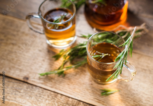 Foto op Canvas Koffie Herbal tea with aromatic rosemary on wood table