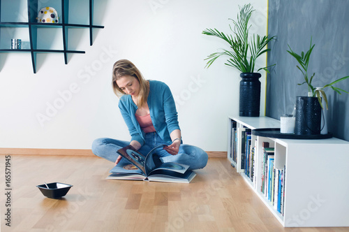 Pretty woman sitting on the floor, reading magazine and eating asian food Poster