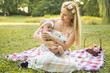 Beautiful happy mother hugging baby girl with love outdoors.