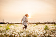 woman running free in dandelion field at sunset in summer day - 165580368