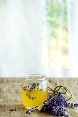 Organic raw honey in glass jar flavored with lavender flowers, standing on table with sackcloth. Rustic style, day light