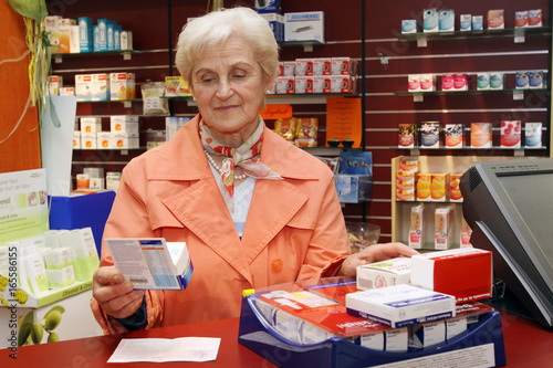 Tuinposter Apotheek Eine Rentnerin begutachtet ein Produkt in der Apotheke
