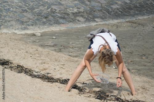 Frau sammelt Muscheln und Krebse an der Nordseeküste