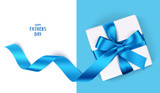 Decorative gift box with blue bow and long ribbon. Happy Father's Day text. Top view - 165599383