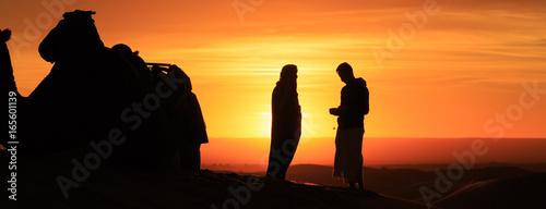 Poster Oranje eclat silhouette of men standing in the desert at sunset