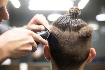 Barber in man hair salon gives trendy hipster millennial haircut, with shaved sides and manbun on top