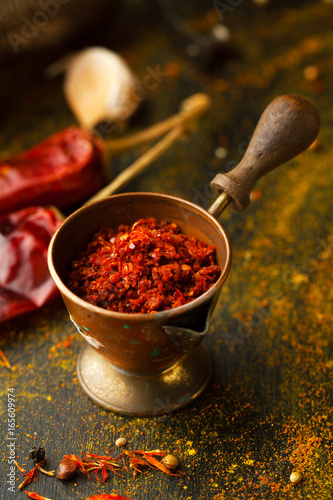 Chili pepper spices in a spoon on a dark