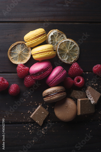 Foto op Aluminium Macarons Group of colorful macarons with their ingredients over a wooden table