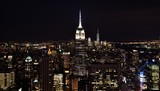 The Empire State Building, One World Trade Center, and the skyline of downtown Manhattan at night.