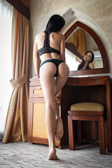 Perfect girl in a sexy black lingerie showing her beautiful ass