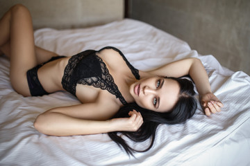 Perfect girl in a sexy black lingerie lying on the bed