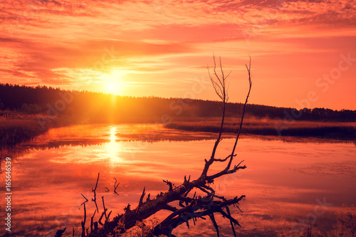 Orange sunset over the lake. Misty evening, rural landscape, wilderness, mystical feeling