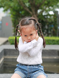 Child girl shutting down her ears, holding her hands covers ears not to hear.