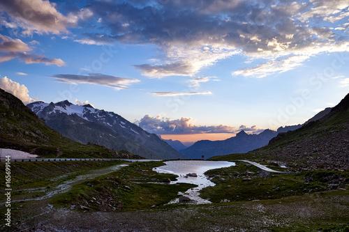 Sustenpass Bergsee Passstrasse Gebirge Himmel Wolken Abendrot nach Sommergewitter