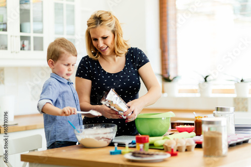Wall mural Smart cute child helping mother in kitchen