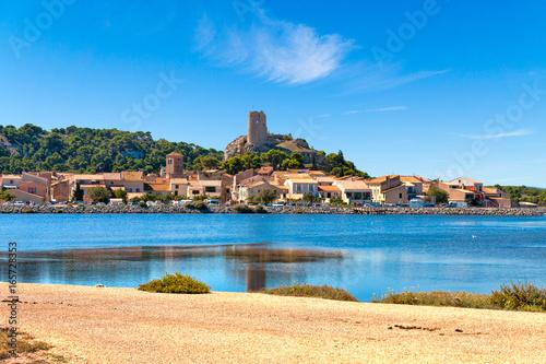 Fototapeta Blick auf den Ort Gruissan mit der Burgruine Tour Barberousse und dem Gewässer Etang de Gruissan in Südfrankreich.