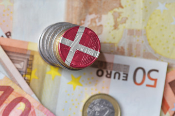 euro coin with national flag of denmark on the euro money banknotes background.