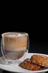 Coffee and biscuits. Cappuccino in glass mug with home made cookies.