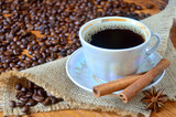 A cup of black coffee with cinnamon bark among the sackcloth, whole grains of coffee and anise star on a wooden table