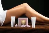 Présentation de tubes de crème et d'une bougie devant les jambes bronzée d'une femme - 165785782