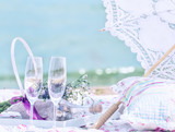 Picnic on the beach. Openwork umbrella, pillow, glasses, in the background a beautiful sea view.