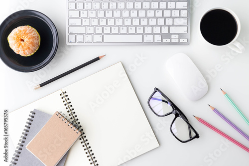 Modern white office desk top table with computer laptop, a cup of coffee, notebook and other supplies. Top view with copy space on white background. Top view, flat lay. © morepiixel