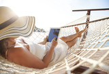 Woman using tablet pc on beach - 165799334