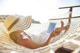 Woman using tablet pc on beach - 165799338