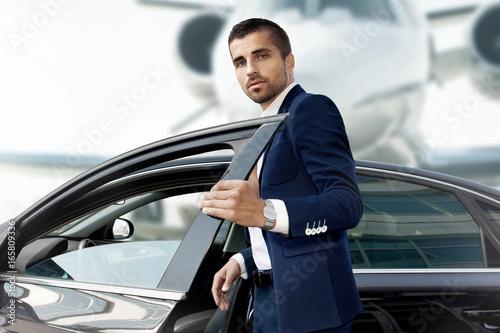 Fototapeta Businessman opens the car door