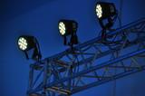 Drei Scheinwerfer auf einem Gerüst vor tiefblauem Hintergrund