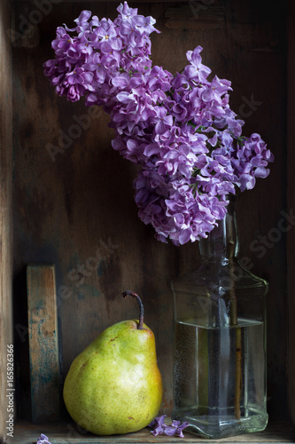 Painting concept. Stylish artist's table with brushes, wooden box, blank, pear, lilac branch. Creative composition in Shabby chic style.