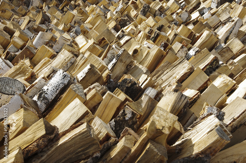 Pile of stacked firewood prepared for fireplace and boiler