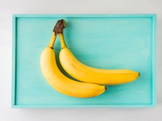 Two bananas on green pastel wooden background