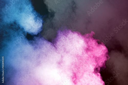 Abstract art colored powder on black background. Frozen abstract movement of dust explosion multiple colors on black background. Stop the movement of multicolored powder on dark background. - 165845305