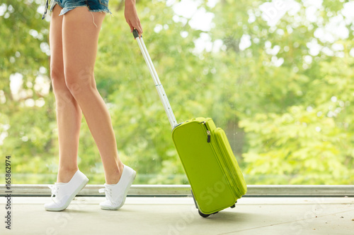 Fototapeta Attractive woman legs walking with green suitcase