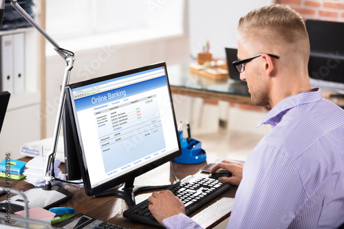 Fototapeta Businessman Doing Online Banking In Office