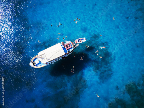 Top view of tourists enjoy swimming in turquoise clear waters in beautiful sea.
