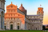 Złote światło słoneczne trafiło na szczycie Krzywej Wieży i katedry w Pizie we Włoszech
