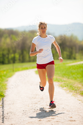 Woman runner runs - workout in spring