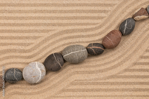 Foto op Plexiglas Stenen in het Zand Still life. Striped stones lying on striped sand.